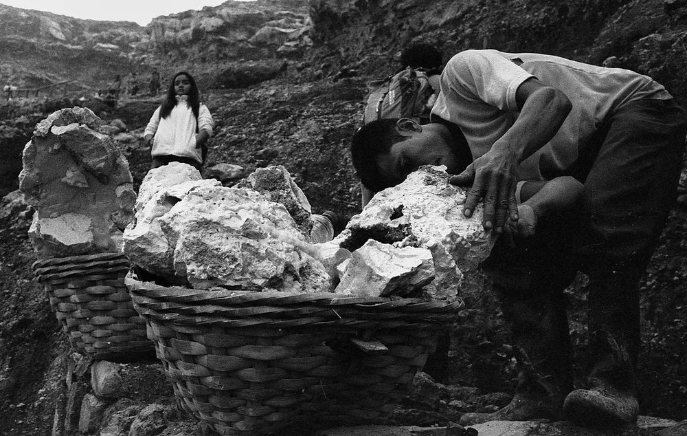 A miner prepares his freshly harvested sulfur on a basket which he will carry to the peak where other miners await him.