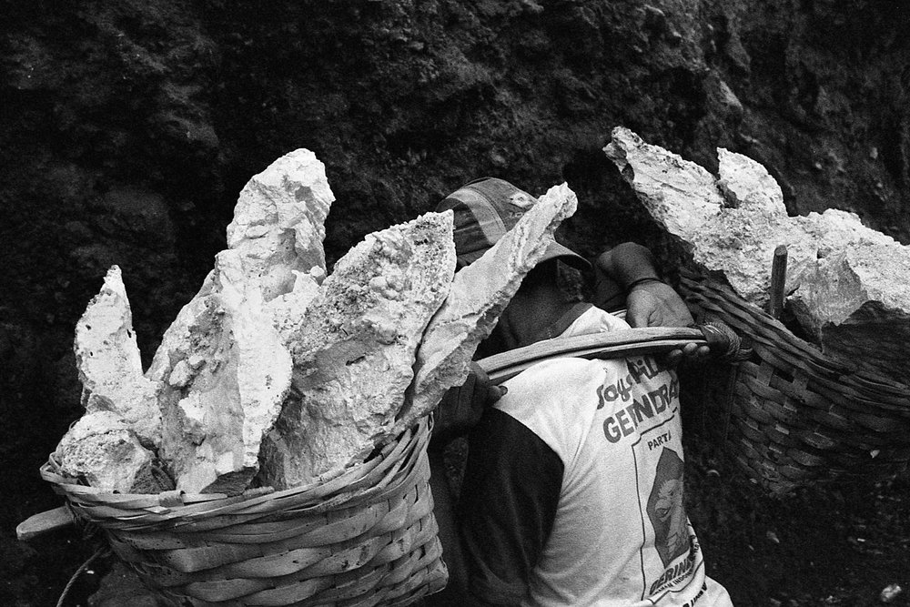 A miner carrying a basket full of sulfur that is estimated to be 70kg in weight.