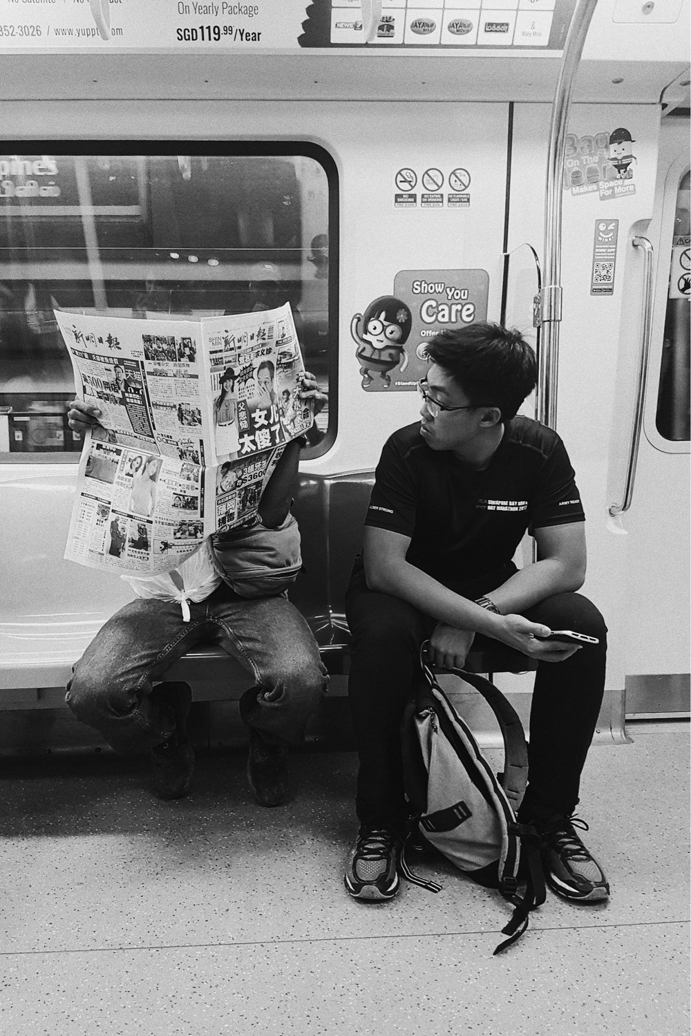 Younger guy reads the newspaper that the older guy is holding up for himself