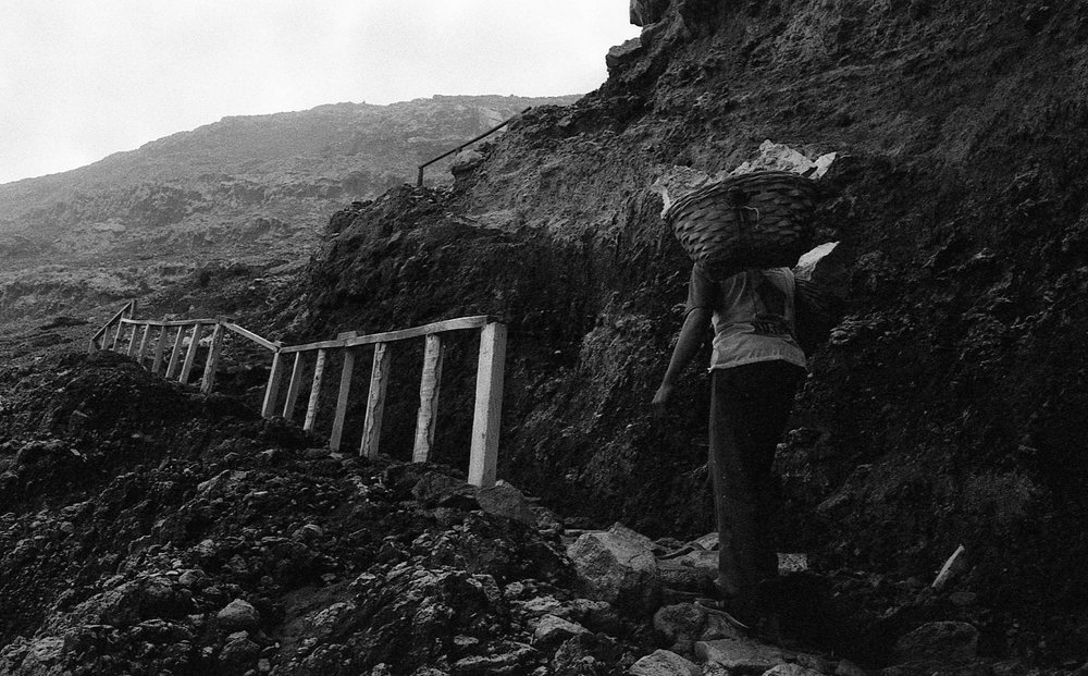 A miner hikes an uneven terrain back to the summit with the sulfur he mined across his shoulders.