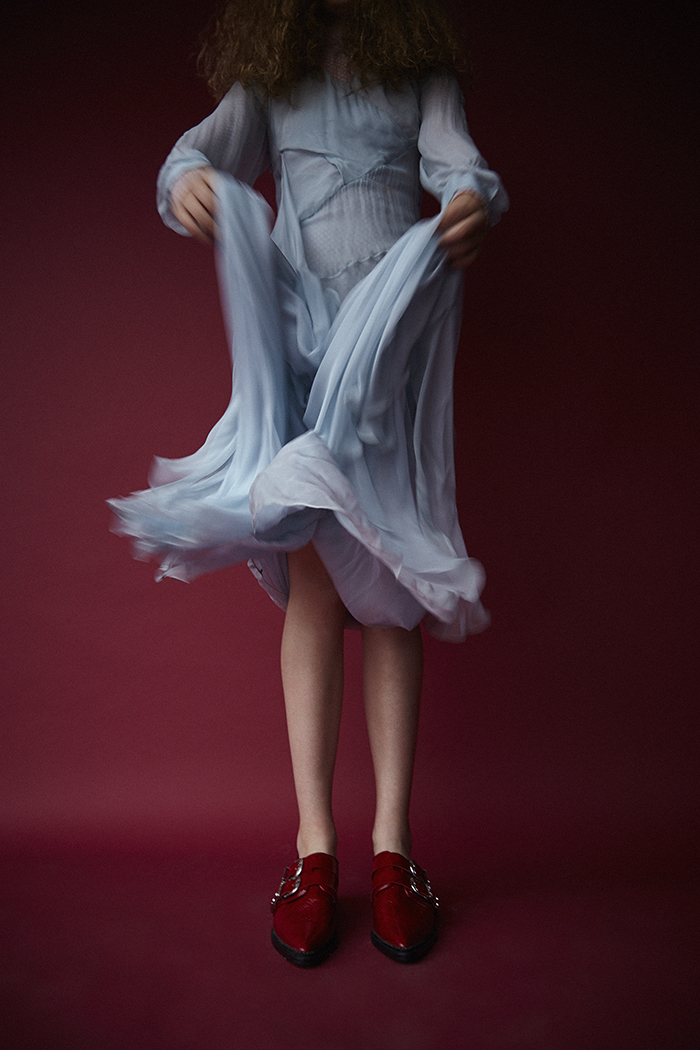Erin wears powder blue sheer dress by Vionnet and red flat shoes with buckles by Toga