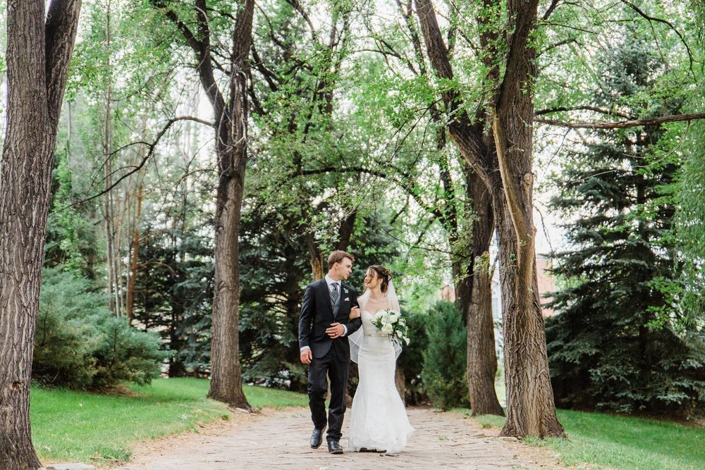 Couple walking arm in arm down a tree covered path.