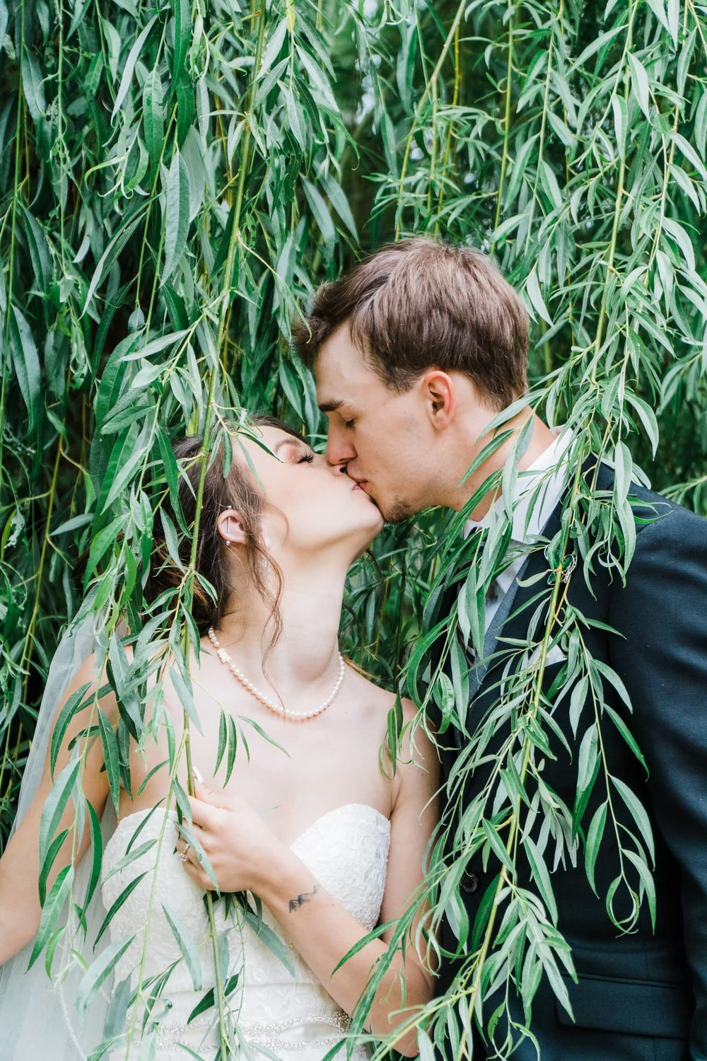 Bride and groom kissing among willow tree branches.