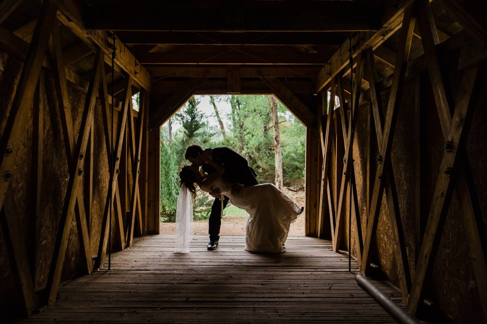 Groom dipping bride and kissing under a covered bridge, silhouetted against bright outside light.