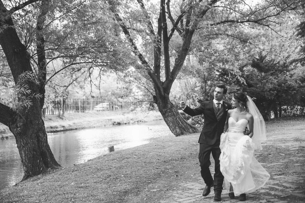 Black and white photo of couple walking down a tree-covered path, next to a stream.
