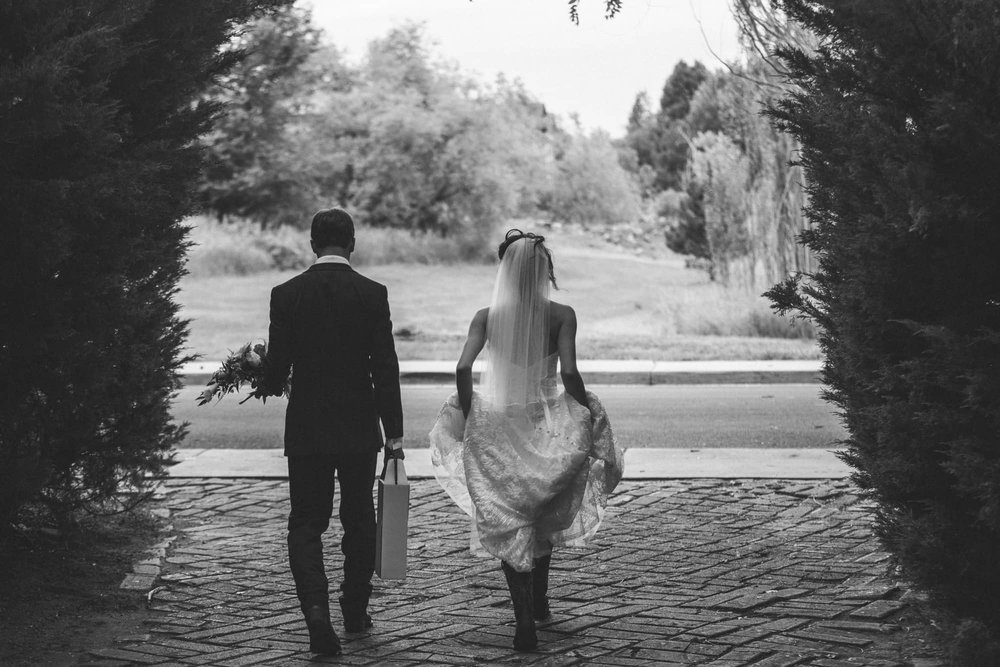Black and white shot of bride and groom walking out of park onto a road.