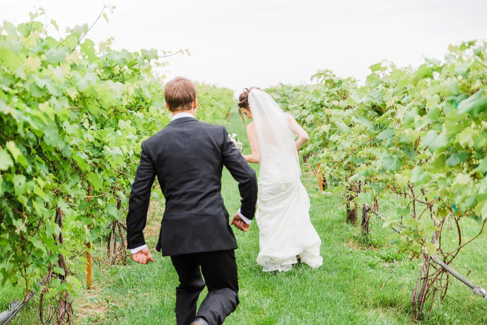 Groom playfully chasing bride down a row of a vineyard.