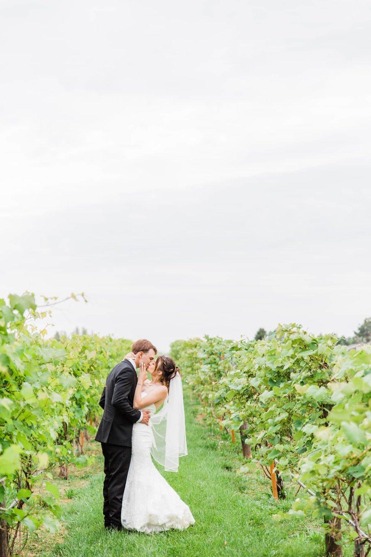 Wide vertical shot of bride and groom kissing in a vineyard.