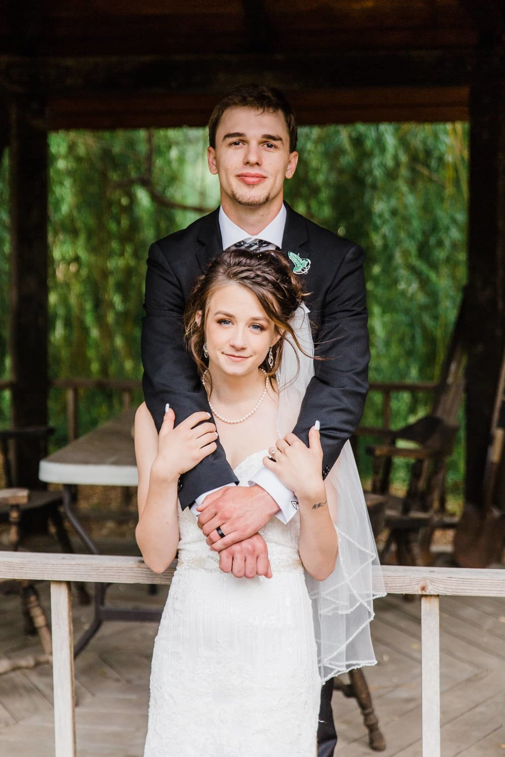 Groom standing behind bride with arms wrapped around her.