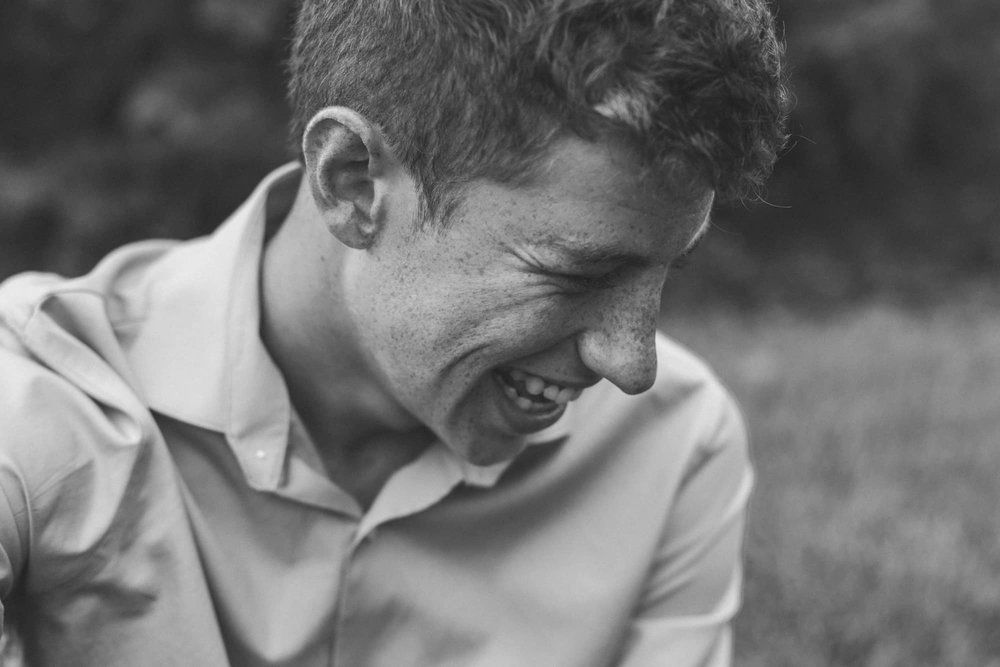 Black and white portrait of young man laughing.