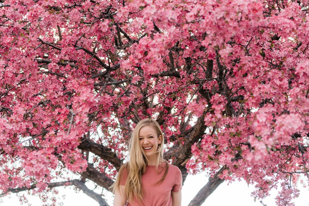 Portrait of a young woman standing under a tree with pink blossums.