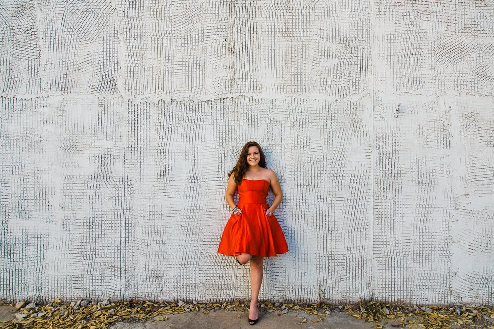 Wide shot of high school senior girl in a bright red dress leaning against a texture white wall.