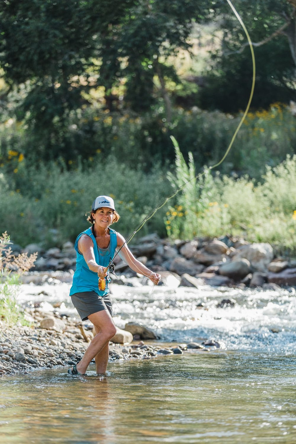 Wide shot of a woman fly fishing along the edge of a river with a concentrated look on her face.