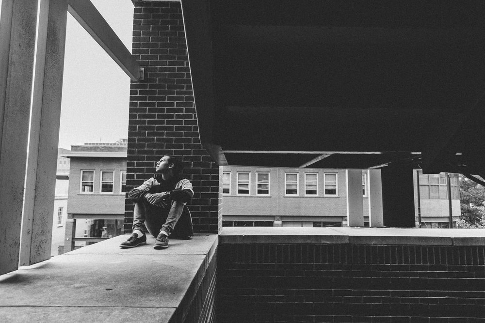 Wide portrait of a young man sitting on the ledge of a stair well and looking up, in black and white.