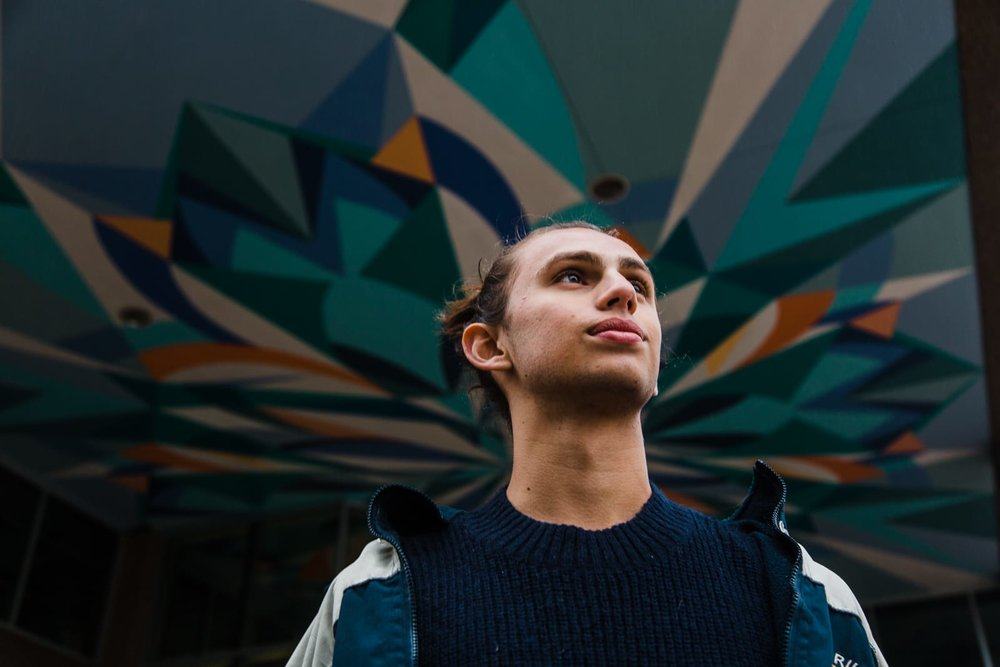 Medium close up portrait of a young man, shot from below, with a colorful geometric pattern in the background.