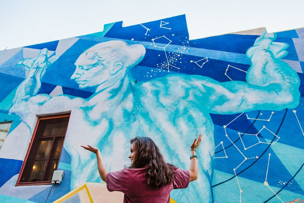 Wide portrait of young woman standing in front of a mural of Atlas and mimicking his pose.