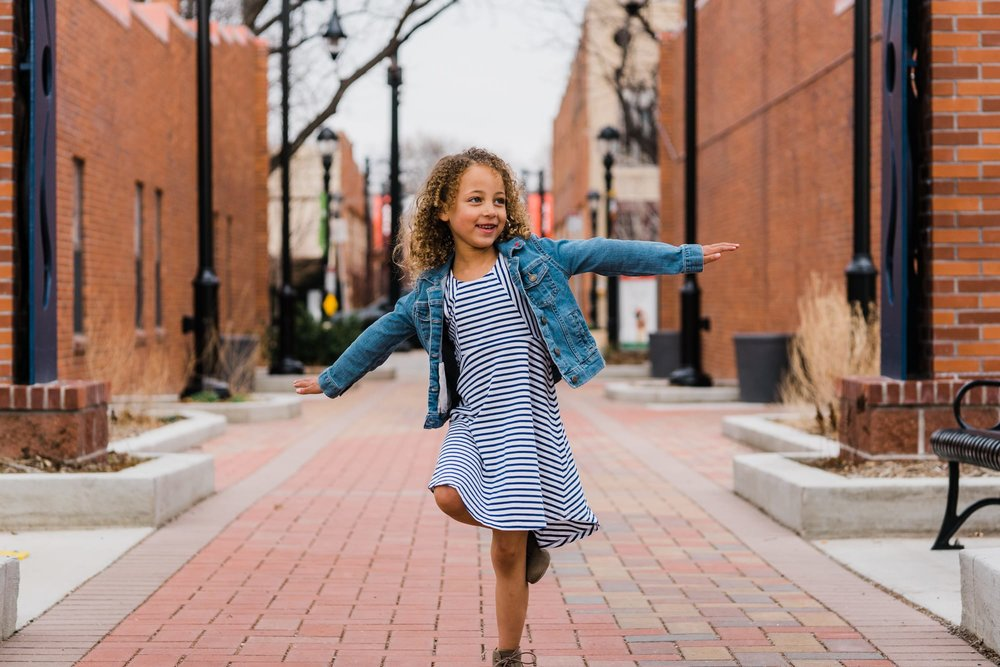 Wide portrait of a girl spinning in an alley.