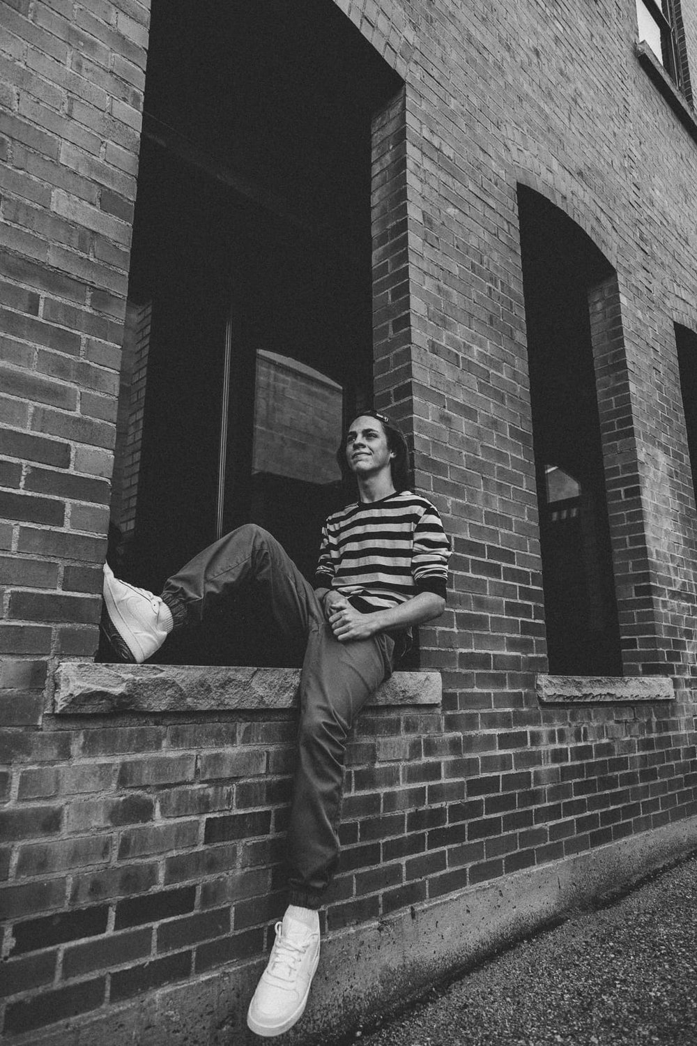 Wide portrait of a young man sitting on a ledge and letting one leg dangle, in black and white.