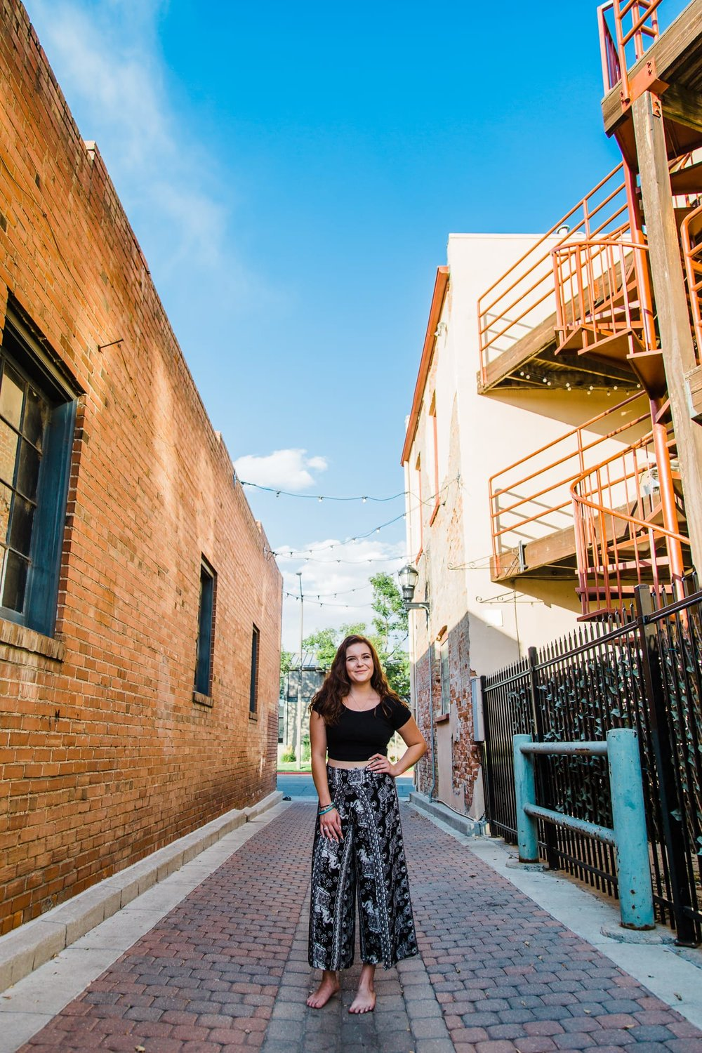 Wide portrait of a young woman standing in an alley with her hand on her hip.