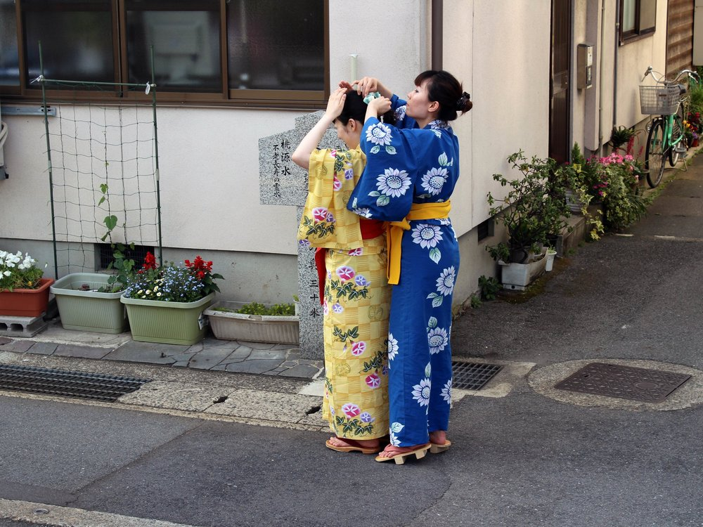 Two Japanese women adjusting their outfits as they stroll through town