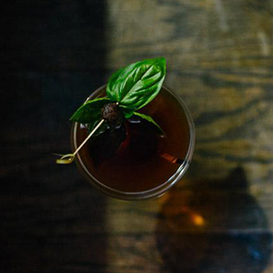JACKIE TREEHORN   • 1 oz. Rittenhouse Rye • 1 oz. Overholdt Rye • .75 oz. Averna • .5 oz. Vedrenne Cacao • 1 Dash Hazelnut Cherry Bitters or Angostura Bitters  • 1. Combine all ingredients into a mixing glass over ice and stir until chilled. • 2. Strain into a coupe glass. • 3. Garnish with basil and a cherry or chocolate.