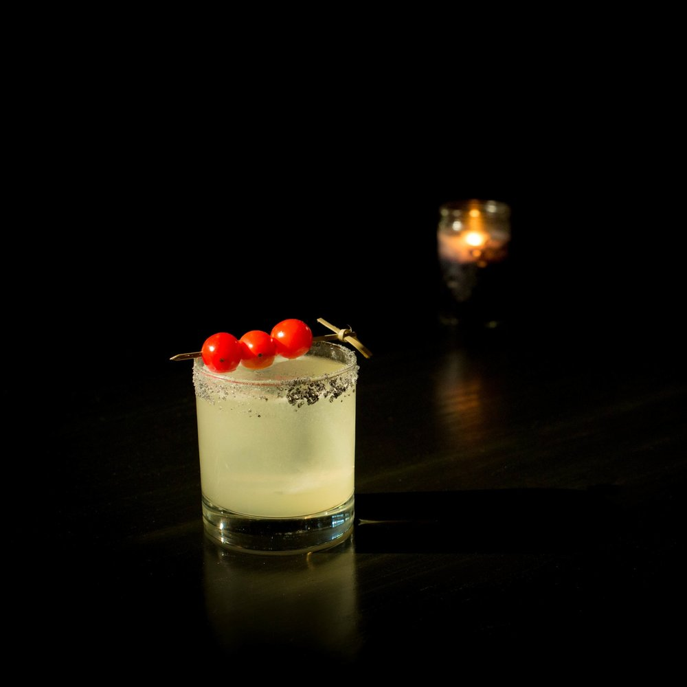 TOM TOM   • 1.25 oz. Sotol • .75 oz. Ancho Verde • .75 oz. lime juice • .5 oz. Creme de Cacao  • 1. In a cocktail shaker, muddle one quarter tomatillo with a pinch of salt. • 2. Add remaining ingredients and shake with ice. • 3. Fine strain into a lava salt rimmed rocks glass. • 4. Garnish with 3 skewered grape tomatoes.