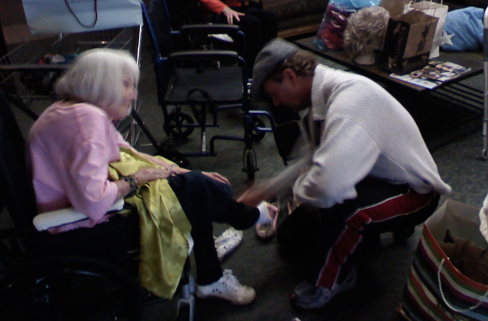 Actor John Schneider helps an elderly resident at The Motion Picture Home try on a pair of donated tennis shoes.