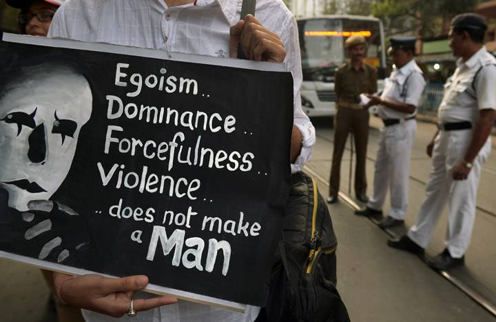 An Indian social activist holds a placard as policemen (background R) look on during a rally on the International Day for the Elimination of Violence against Women in Kolkata on November 25, 2013. Getty Images.