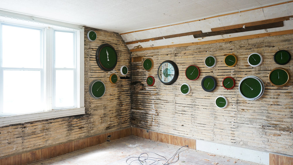 Ape_Bleakney_RoomsToLet_'Sixth Extinction (11.57)' (1), Installation (Clocks, Artificial Grass, Spraypaint, Audio), 2017.jpg