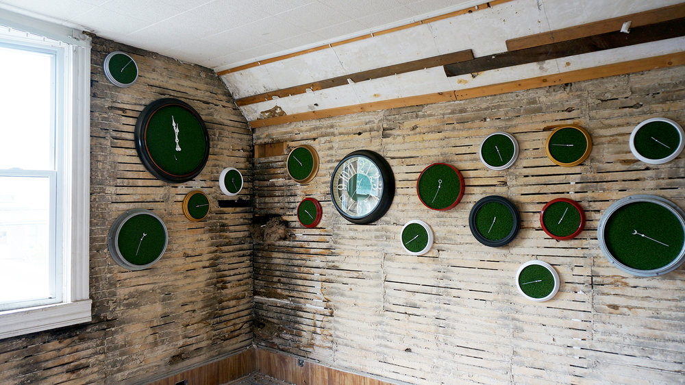 Ape_Bleakney_RoomsToLet_'Sixth Extinction (11.57)' (2), Installation (Clocks, Artificial Grass, Spraypaint, Audio), 2017.jpg