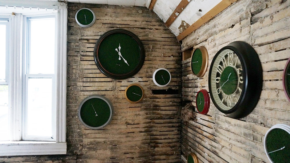 Ape_Bleakney_RoomsToLet_'Sixth Extinction (11.57)' (10), Installation (Clocks, Artificial Grass, Spraypaint, Audio), 2017.jpg