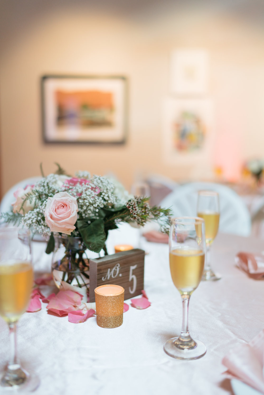 The champagne glasses provided by our caterer, gold votives (Michaels craft store), candles (Michael's craft store), table number blocks (T.J. Maxx), arrangements by mom and her best friend, along with scattered rose petals. I loved how they turned out!