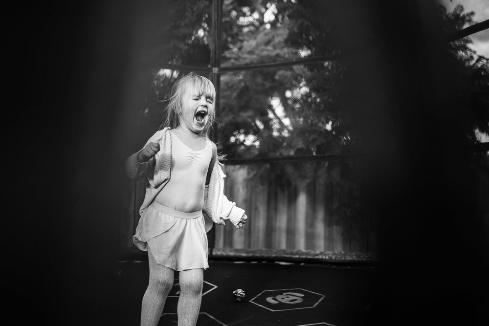 Girl screaming on trampoline.