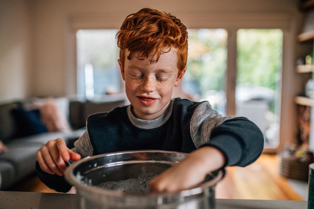 Red headed boy stirring batter.