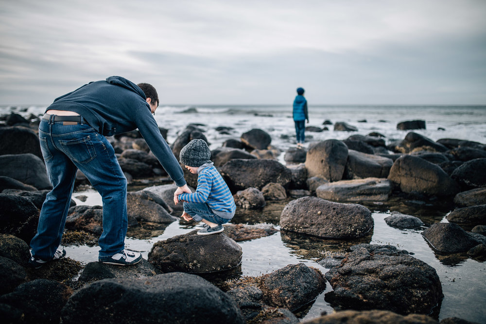 father comforting son on rocks at beach (1 of 1).jpg