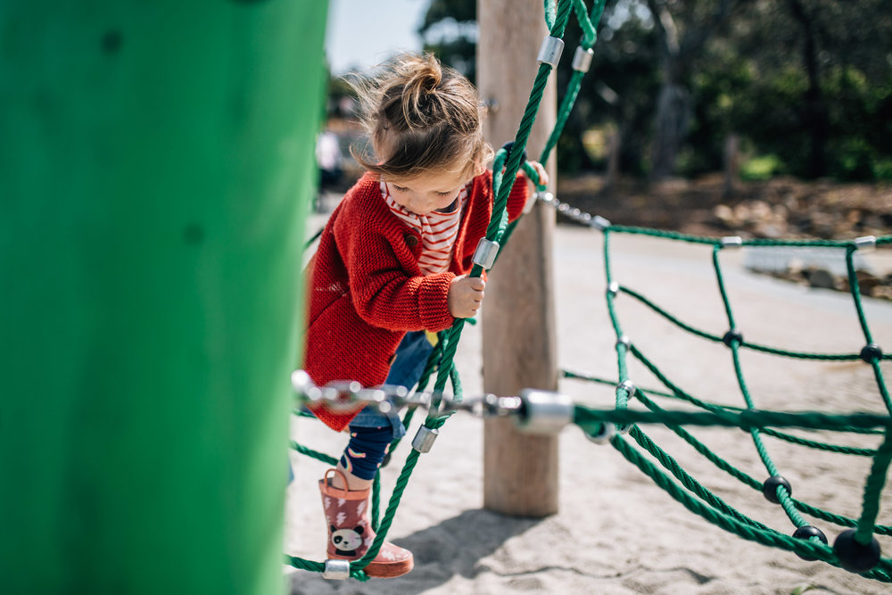 little girl in red cardigan climbing play equipment IV (1 of 1).jpg