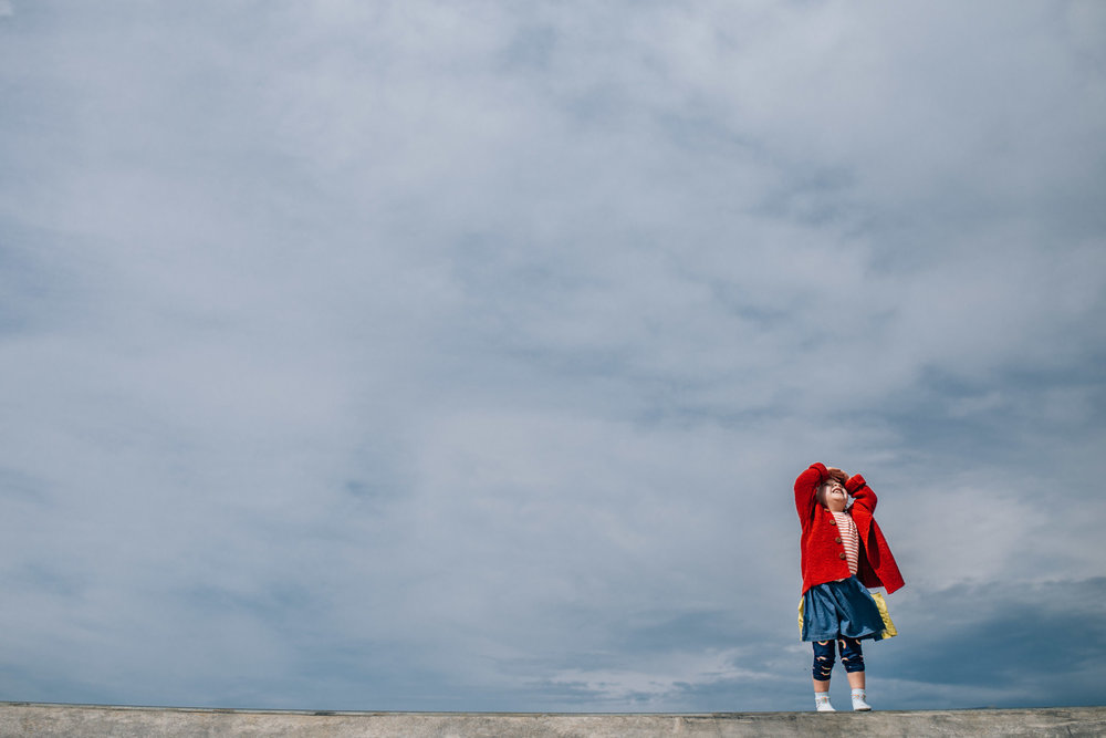 little girl in red cardigan staring at the sky (1 of 1).jpg