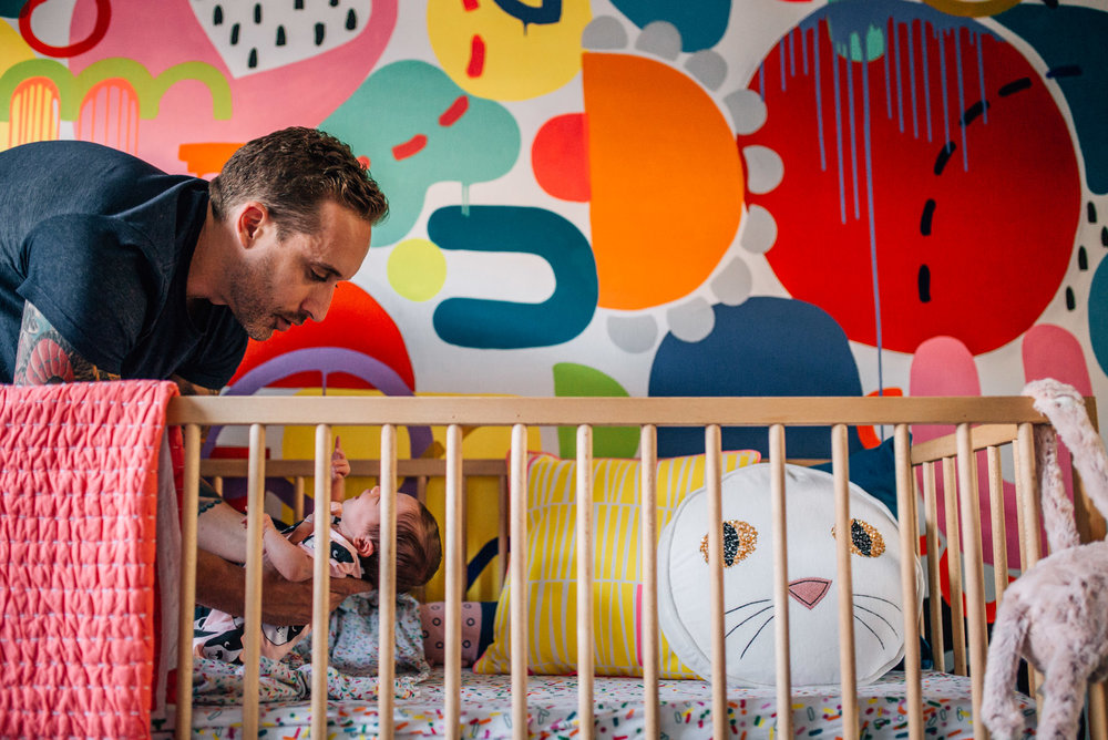 father lifting baby daughter out of crib (1 of 1).jpg