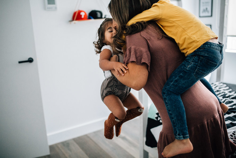 little boy hitching ride on mothers back while she lifts daughter (1 of 1).jpg