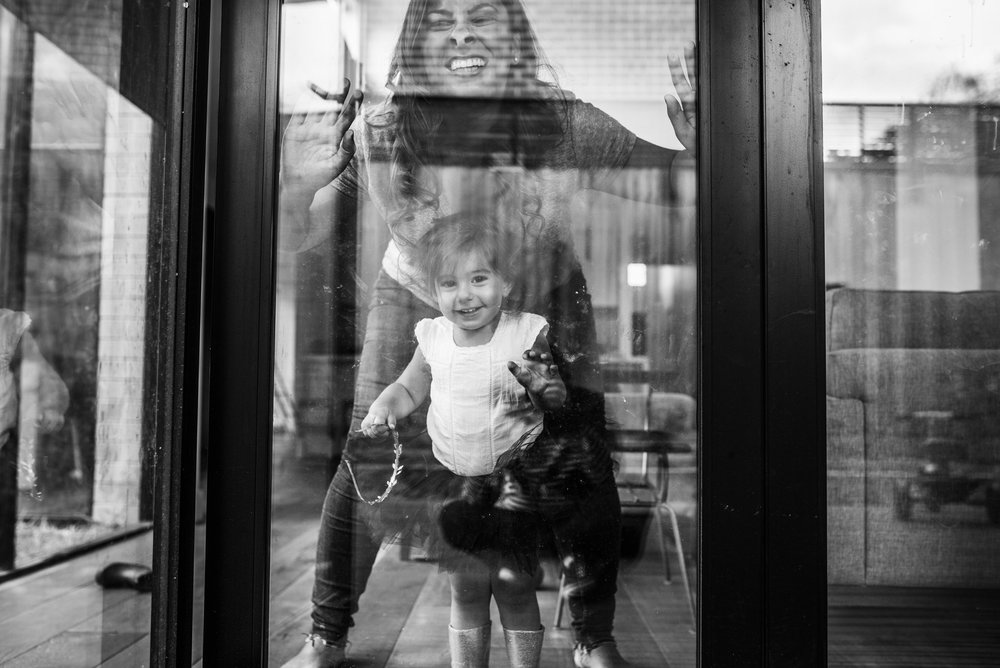 mother and daughter being silly behind glass (1 of 1).jpg