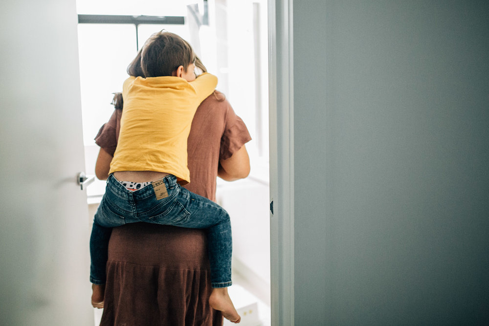 mother piggy backing son into bathroom (1 of 1).jpg