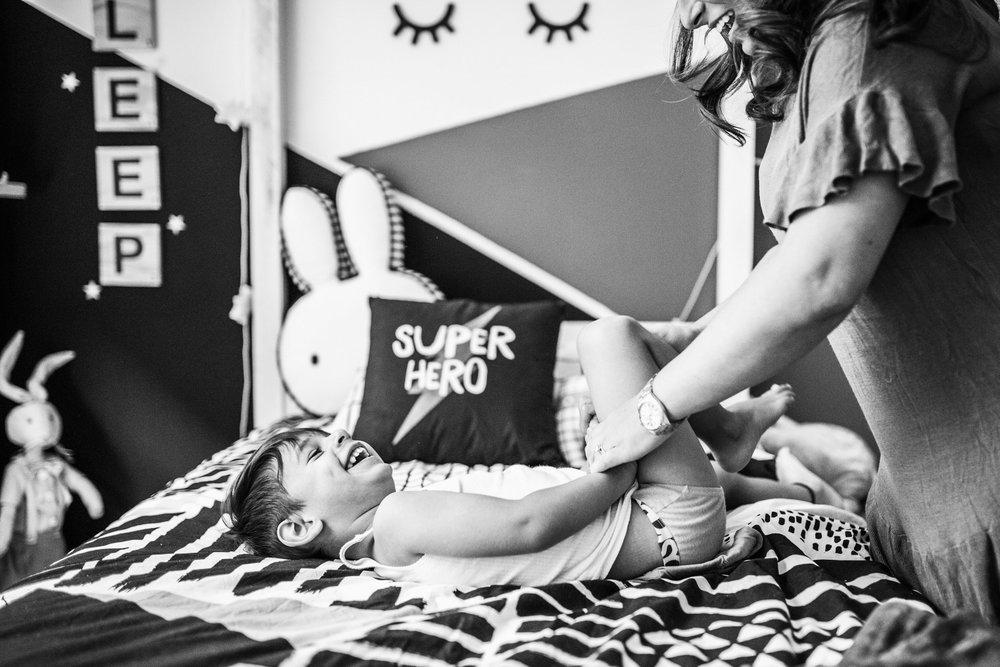 mother tickling son as she dresses him (1 of 1).jpg