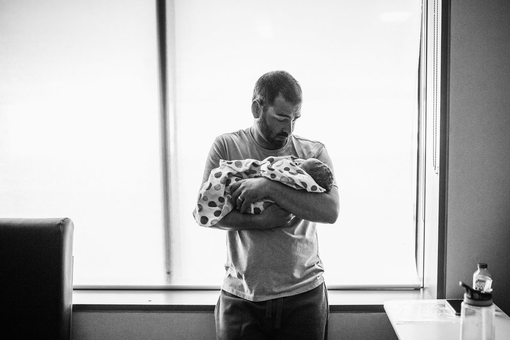 father standing with newborn baby by window BW (1 of 1).jpg