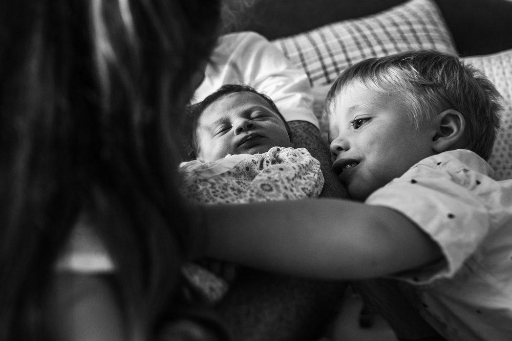 toddler-boy-snugglig-into-newborn-baby-sister (1 of 1).jpg