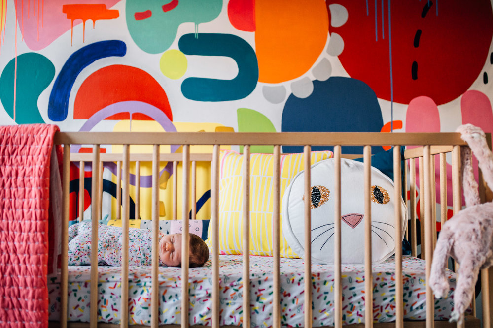 newborn swaddled in nursery with rainbow coloured wall art (1 of 1).jpg