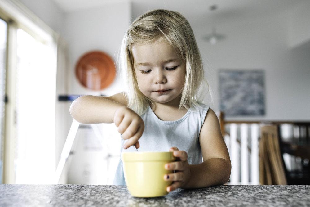 little-girl-eating-pancake-batter-from-yellow-ramikin.jpg
