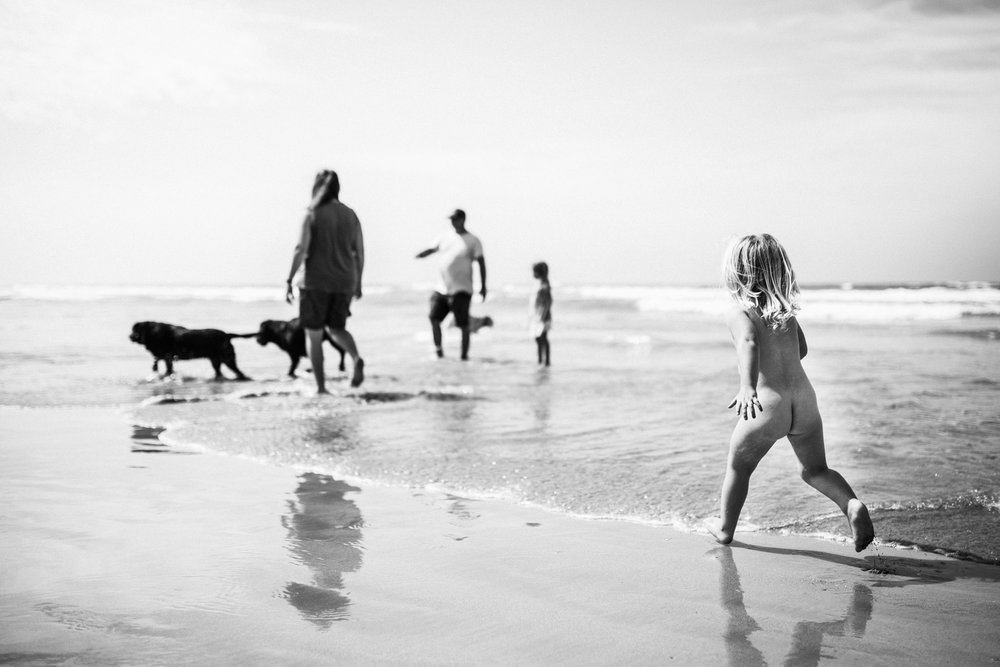 little-girl-running-naked-on-the-sand-with-family-in-background-BW (1 of 1).jpg