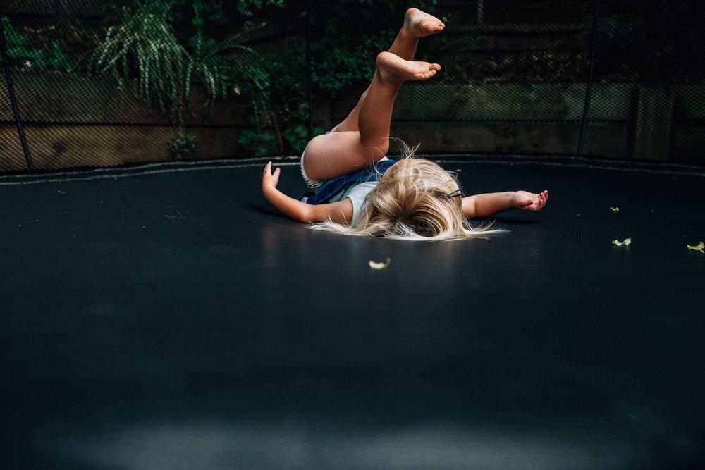 little-girl-flopping-down-onto-trampoline (1 of 1).jpg