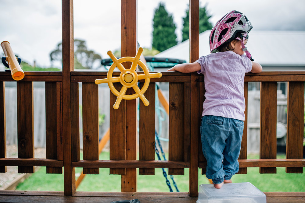 toddler-girl-in-bicycle-helmet-looking-out-over-fort-wall (1 of 1).jpg