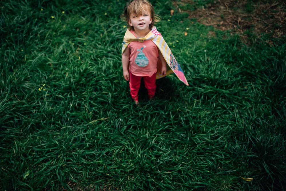 little girl in super hero cape in backyard (1 of 1).jpg